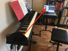 Picture of piano with arrow pointing to computer screen, taken by the author.